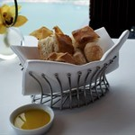 Four fresh breads (baked parmesan crisps, focaccia, sourdough, ciabatta) and two kinds of olive